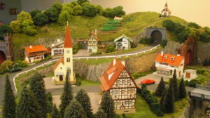 The village with the vineyard on the hill. This uses the Busch vineyard kit built by the client. The client also added the guardrail.